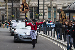 "London, April 16th 2016. A woman carrying a poo-shaped ""1%"" placard marches in front of traffic as thousands of people supported by trade unions and other rights organisations demonstrate against the policies of the Tory government, including austerity and perceived favouring of ""the rich"" over ""the poor""."
