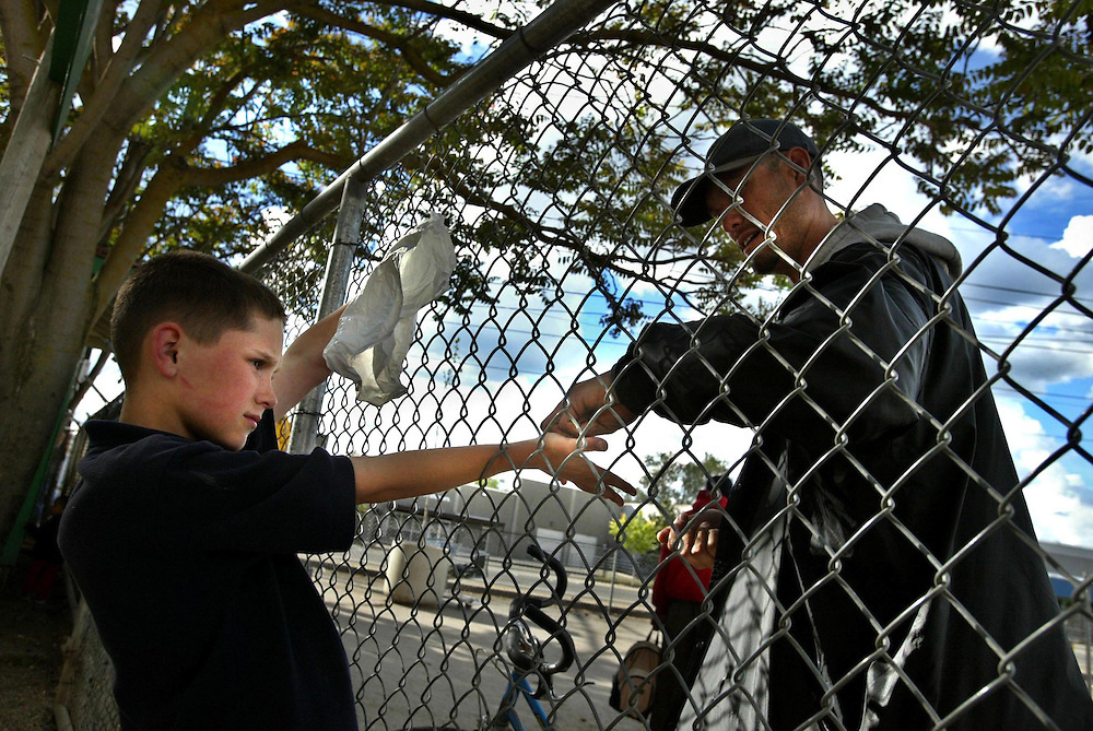 Loaves and Fishes, Paul Bishop 10, gets some change from his father through a chain link fence that separates the two of them. The children are separated from there fathers several hours before heading out to the women and children overflow shelter. .