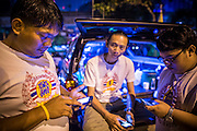 "30 NOVEMBER 2012 - BANGKOK, THAILAND: Medics with the Ruamkatanyu Foundation check their smart phones between calls near the Ekamai BTS stop during a Friday night shift. The Ruamkatanyu Foundation was started more than 60 years ago as a charitable organisation that collected the dead and transported them to the nearest facility. Crews sometimes found that the person they had been called to collect wasn't dead, and they were called upon to provide emergency medical care. That's how the foundation medical and rescue service was started. The foundation has 7,000 volunteers nationwide and along with the larger Poh Teck Tung Foundation, is one of the two largest rescue services in the country. The volunteer crews were once dubbed Bangkok's ""Body Snatchers"" but they do much more than that now.    PHOTO BY JACK KURTZ"
