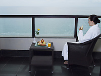 beautiful calm and serene woman in palace hotel room at the balcony facing the sea