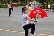 07 JULY 2011 - BANGKOK, THAILAND:   Women exercise early in the morning with folding fans in Lumphini Park in Bangkok. Lumphini Park (also Lumpini or Lumpinee) is a 360-rai (57.6-hectare or 142-acre) park in Bangkok, Thailand. The park offers open public space, trees and playgrounds in the Thai capital and contains an artificial lake where visitors can rent a variety of boats. Paths around the park totalling approximately 2.5 km in length are a popular area for evening joggers. Lumpini Park was created in the 1920s by King Rama VI on royal property. A statue of the king stands at the southwestern entrance to the park. It was named for Lumbini, the birthplace of the Buddha in Nepal, and at the time of its creation stood on the outskirts of the city. Today it lies in the heart of the main business district and is in the Lumphini sub-district, on the north side of Rama IV Road, between Ratchadamri Road and Witthayu (Wireless) Road.     PHOTO BY JACK KURTZ