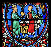 The father gives the inheritance to the younger son, who takes a gold vessel and puts gold coins in his cloak, from the Parable of the Prodigal Son stained glass window, in the north transept of Chartres Cathedral, Eure-et-Loir, France. This window follows the parable as told by St Luke in his gospel. It is thought to have been donated by courtesans, who feature in 11 of the 30 sections. Chartres cathedral was built 1194-1250 and is a fine example of Gothic architecture. Most of its windows date from 1205-40 although a few earlier 12th century examples are also intact. It was declared a UNESCO World Heritage Site in 1979. Picture by Manuel Cohen