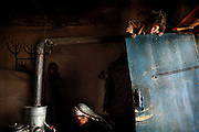 Maryam, 38, (Centre) is lighting the family's wood stove inside their cave while, Hamidah, 6, (Left) and her sister Fatemah, 12, (Right) are awaiting for tea in the early hours of the morning, in Bamyan, central Afghanistan, an area mostly populated by Hazaras. A historically persecuted minority (15%) due to more lenient Islamic faith and characteristic 'Eastern' lineaments, Hazaras constitute the 70% of Bamyan's population.