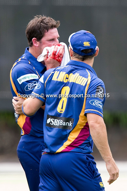 Volts` Bradley Scott leave the filed assisted by  Nathan McCullum  after being struck in the face by a ball hit by Aces` Tarun Nethula in the Auckland Aces v Otago Volts, One Day Ford Trophy Cricket Match, Eden Park, Auckland, New Zealand, Friday, January 02, 2015. Photo: David Rowland/Photosport