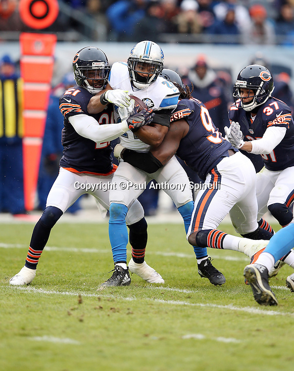 Detroit Lions rookie running back Ameer Abdullah (21) gets gang tackled by Chicago Bears outside linebacker Willie Young (97) and Chicago Bears cornerback Tracy Porter (21) during the NFL week 17 regular season football game against the Chicago Bears on Sunday, Jan. 3, 2016 in Chicago. The Lions won the game 24-20. (©Paul Anthony Spinelli)