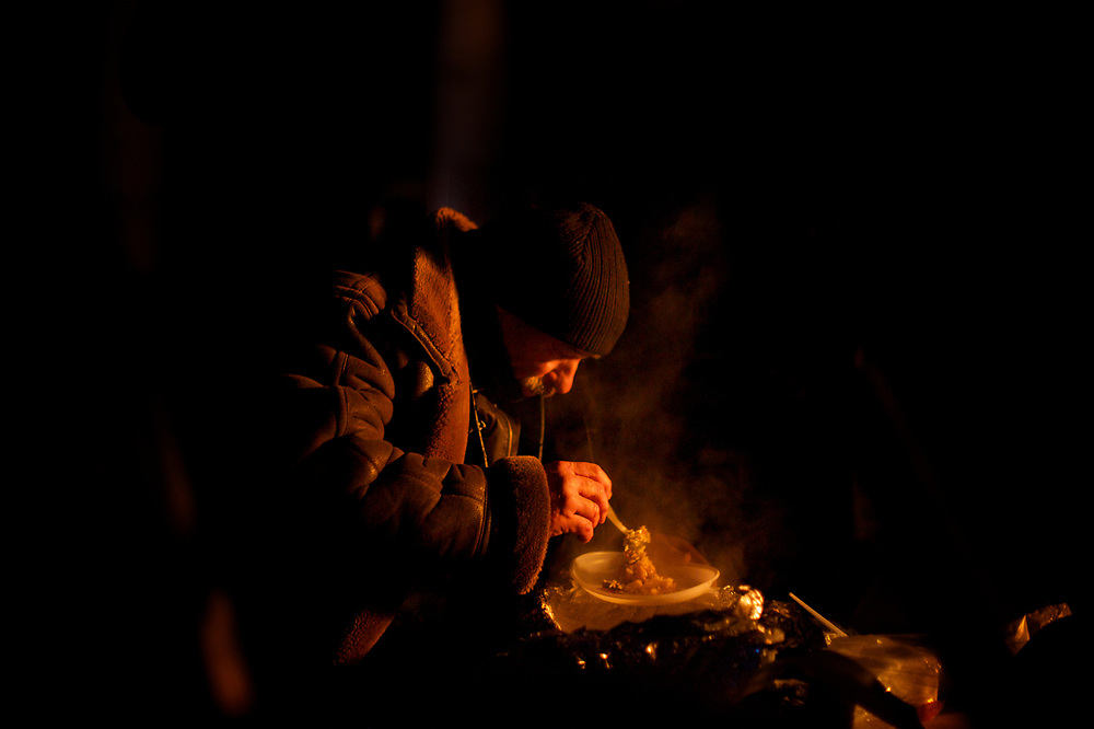 January 27, 2014 - Kiev, Ukraine: A Ukrainian anti-government protestor eats a warm meal while standing guard to a barricade, as demonstrations continue in Kiev's Independence Square. (Paulo Nunes dos Santos)