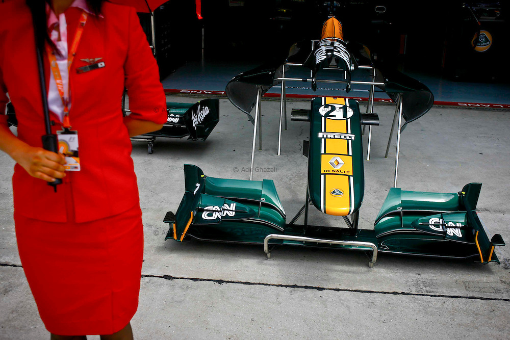 AirAsia Airlines's stewardess stand in front of the Team Lotus's pit area during the Malaysian Formula One Grand Prix in Sepang, Malaysia, Sunday, April 10, 2011.