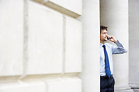 Businessman on cell phone outside building by pillar