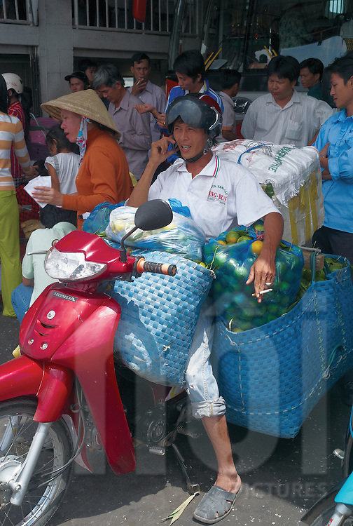 Vietnamese man sitting on a motorbike heavily loaded of fruits. Ferry going to Long Xuyen, An Giang Province, Vietnam, Southeast Asia