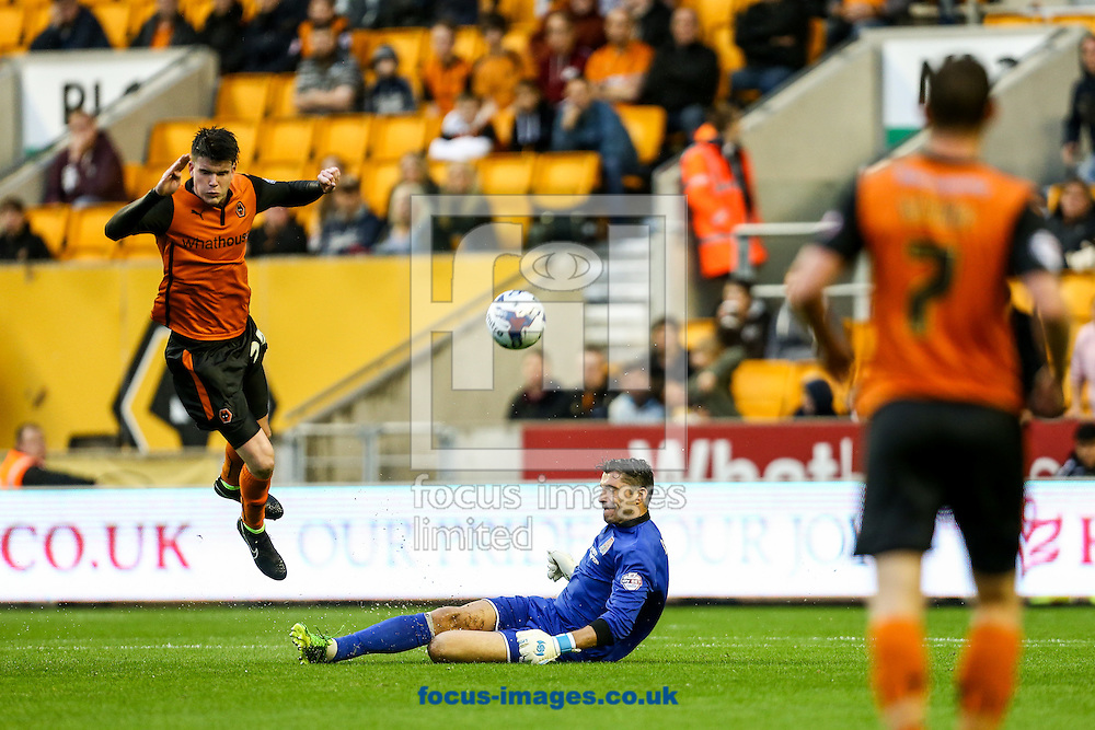 Liam McAlinden of Wolverhampton Wanderers (left) leaps in the air as Matt Duke of Northampton Town (centre) clears the ball  during the Capital One Cup match at Molineux, Wolverhampton<br /> Picture by Andy Kearns/Focus Images Ltd 0781 864 4264<br /> 12/08/2014