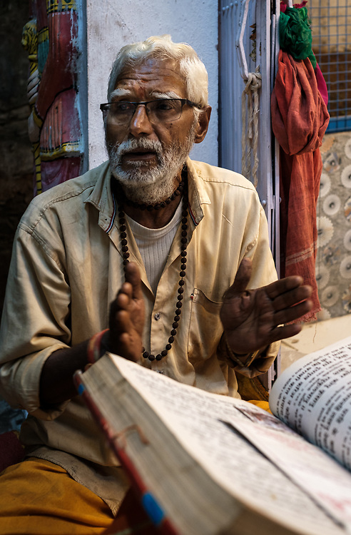 """UDAIPUR, INDIA - CIRCA NOVEMBER 2018: Priest on the street of Udaipur at night. The city is the historic capital of the kingdom of Mewar. Surrounded by Aravali Range, which separates it from Thar Desert, and full of lakes Udapiur is also known as the """"City of Lakes"""" and dubbed as the most romantic spot of the Indian Continent."""