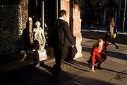Woman picks-up dropped item in front of small girl statue credited to the 19th century Florence-born artist Raffaello Romanelli. Part of a sequence of 4 images showing the woman in red dropping the Oyster card and subsequently bending down and picking it up.