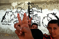 Palestinian youths hold the V for victory sign in front of a militant mural on the streets of Gaza City. (Photo/Scott Dalton)