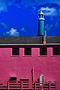 Turquoise lighthouse over a pink dock building, Monterey Bay, California