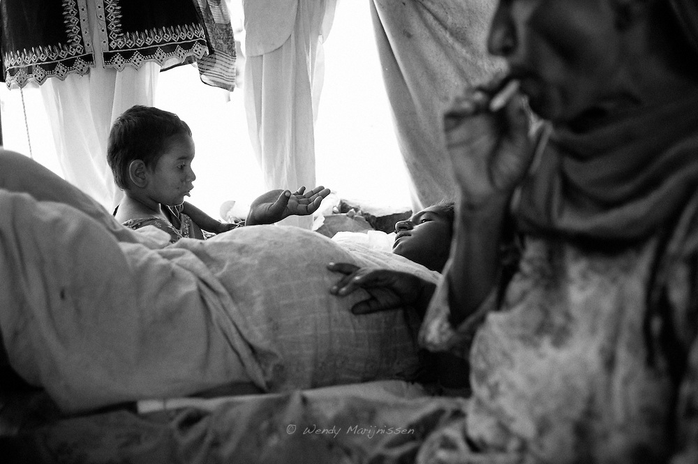 Mehmooda wants to play while Hamida is taking a rest after dinner. Her mother smokes a cigarette and will help take care of the baby once it's born. Karachi, Pakistan, 2010