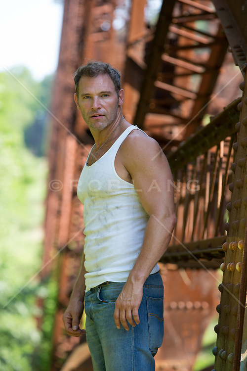 rugged middle aged man on a railroad trestle