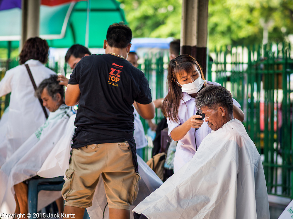 16 APRIL 2015 - BANGKOK, THAILAND:  People get haircuts at a barber school that sets up on the platform at Hua Lamphong Train Station in Bangkok. Travelers get free haircuts and the barber students get to practice on real heads.    PHOTO BY JACK KURTZ