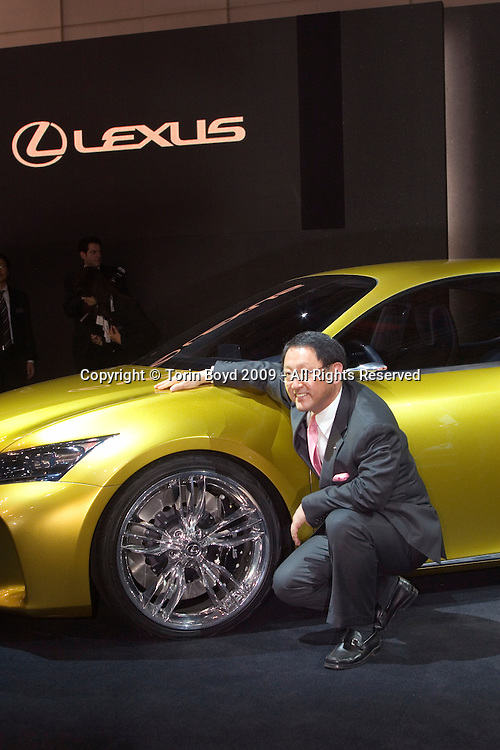"This is the Lexus LF-Ch with Toyota Motor Corp. President Akio Toyoda at the 41st Tokyo Motor Show 2009, Oct 21, 2009 (press day). Unveiled in September 2009 at the Frankfurt Intl. Motor Show, this luxury four door  hybrid hatchback has a ""2.4 L inline-four"" cylinder gasoline engine with electric motor. The interior features wood, polished aluminum, and semi-aniline leather, along with paddle shifters, a turbine-style instrument panel, and Lexus' Remote Touch control interface with pop-up information screen. The Tokyo Motor Show is a biannual auto show. This year's event runs from Oct. 23, 2007 to Nov. 4, 2009 and the theme of this year's show is ""Fun Driving for Us, Eco Driving for Earth"". However even with this upbeat theme, many international auto makers were conspicuously absent due to the worldwide slump in auto sales."
