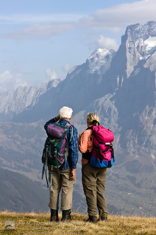 Two older hikers wearing backpacks take in the alpine view of Grindelwald atop Männlichen