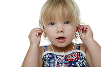 21 July 2008: Two year old toddler Lucy Berg on a white background in studio with a small green iPod shuffle and white earphones. MP3 music technology.