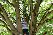 A nine year-old boy squats in his den near a drying out pond in woods near Nailsea, on 21st April 2019, in Nailsea, North Somerset, England