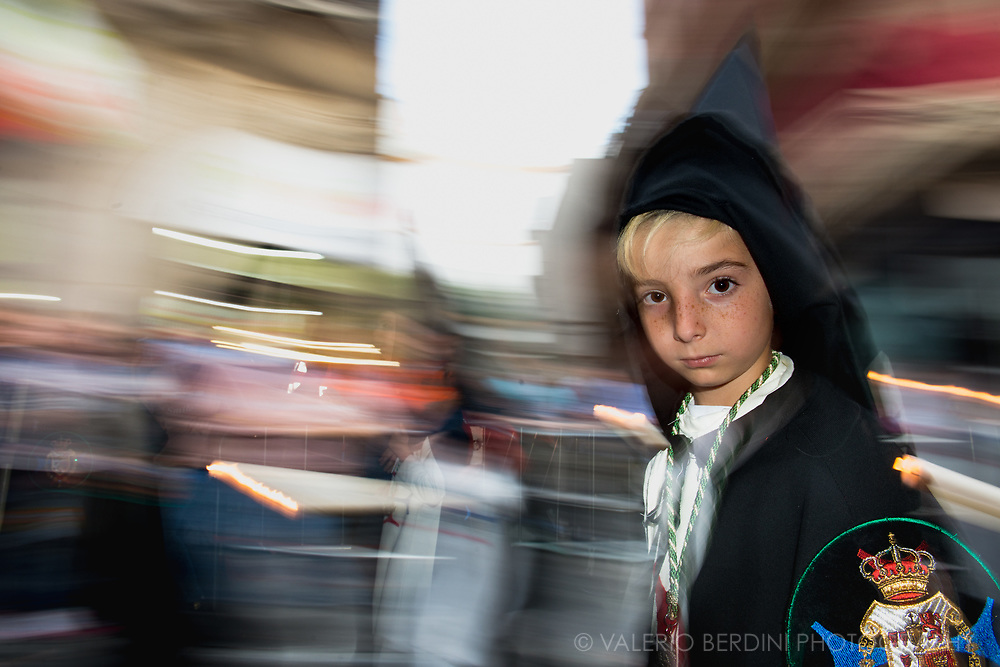 "A child belonging to La Trinidad Brotherhood in the evening of Holy Saturday walk in a central street in Sevilla. Here ""Nazarenos"", dressed with a black ""capirote"", the peculiar conical hat, and a white tunic  perform their penance carrying along the procession either long (and heavy) Paschal candles or wooden crosses."