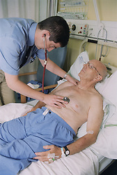 Elderly male patient lying on hospital bed on ENT ward being examined by doctor,