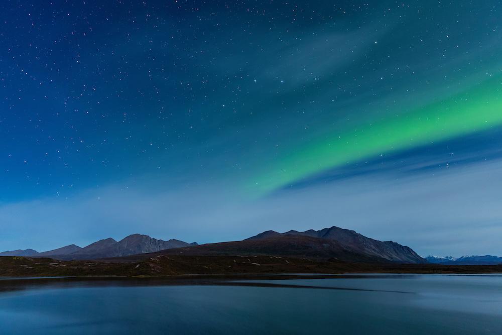 Aurora Borealis above the Alaska Range mountains at Round Tangle Lake along the Denali Highway in Southcentral Alaska. Autumn. Morning.