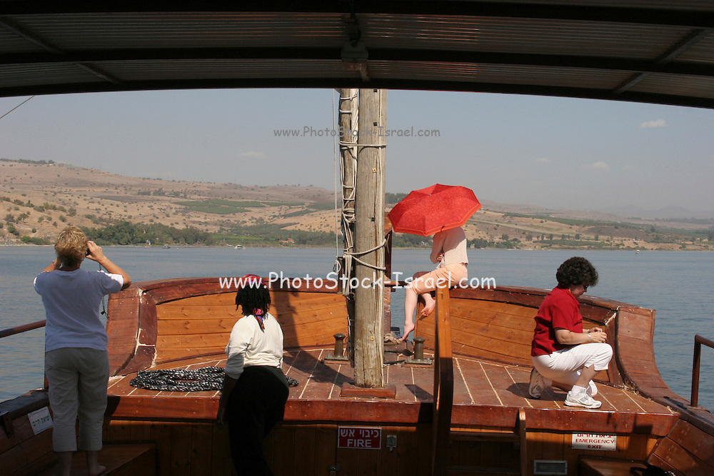 Israel, Sea of Galilee, Tourists aboard a one to one replica of Jesus' Boat. Old wooden boat uncovered in the sea of Galilee, dated to the time of Jesus Christ. The original boat is on display at Kibbutz Ginosar, Israel