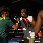 George Khosi training a member of a corporate group using hand pads at the Hillbrow Boxing Club. A small number of private clients and corporate groups, such as this one from Centriq Insurance, help pay the bills, as much of the work Khosi does is for free. A representative of Centriq said the company chooses to bring its staff to Hillbrow, a notorious neighbourhood, to remind them of South Africa's many realities.