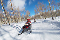 Two couples riding on two snowmobiles along snowy track