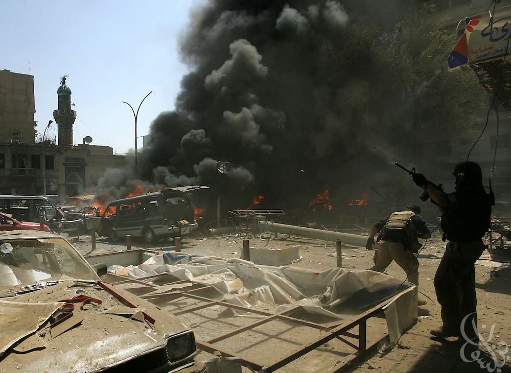 Foreign contractor security guards (r)  take cover just minutes after a suicide car bomber targeted their convoy in Tahrir square in Baghdad May 07, 2005. The bombing, which targeted a passing civilian contractor convoy, killed at least 6 persons and wounded another 30 during the late morning explosion in the busy commercial area in central Baghdad.