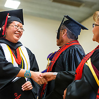 121213       Brian Leddy<br /> Navajo Technical University student Nadine Hicks makes her way across the stage after receiving her accounting degree in Chinle Friday. The graduation was the first for the school as a university.