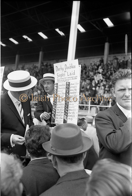 30/06/1962 <br /> 06/30/1962<br /> 30 June 1962<br /> Irish Sweeps Derby at the Curragh Racecourse, Co. Kildare. Bookie Terry Rodgers (left) makes a book at the race meeting.