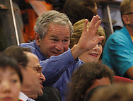 BEIJING, CHINA:  USA President George W. Bush waves at fans as his wife Laura Bush smiles at the USA vs. China basketball game on Sunday,8/11/08   ©2008 Johnny Crawford