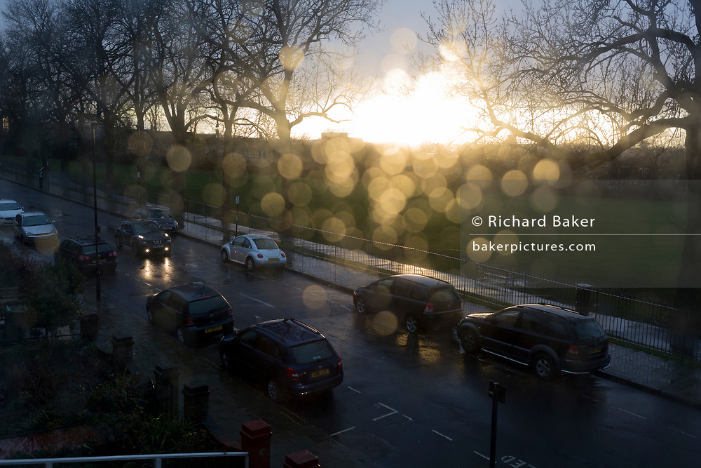 An aerial view of parked cars on a south London street, flooded by sunlight after heavy rainfall with out-of-focus spots of water on the glass of a residential house's window, on 25th February 2020, in London, England.