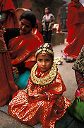 Newar girl in ceremonial clothes at her Ihi ceremony, a mock marriage to the Hindu god Vishnu, in Patan in the Kathmandu Valley, Nepal. Among the Newars, who are the original inhabitants of the Kathmandu Valley, every girl goes through this ceremony sometime between the age of five and ten. The Ihi makes the girl a full member of her father's family and caste and is also said to make sure that she will never become a widow, even if later on her future human husband would die, since she will forever be married to the god Vishnu. The Ihi is therefore for the Newar women a protection against the stigmatization of widows otherwise common in Hindu culture.