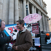 An activist being interviewed by BBC Radio. Day three of the occupation - and the first Monday. The Occupy London Stock Exchange movement was formed in London in solidarity with the US based Occupy Wall Street. The movements are a respons and in anger to what is seen by many as corporate greed and a failed banking system being bailed out by the public, - which in return are suffering austerity measures to make up for the billions of lost money. The movement occupied the St Paul's Square in the City of London Sat Oct 15 after it failed to secure and occupy Pator Noster Square and the Stock Exchnage itself.