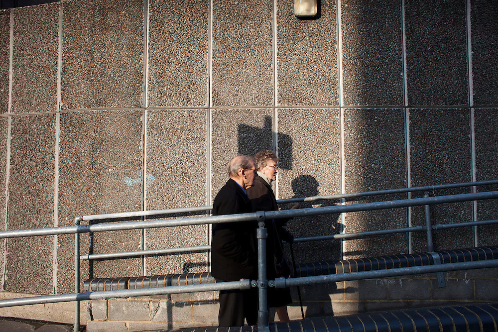 An old couple walking outside Hayward Gallery on the Southbank. London, UK. 2012