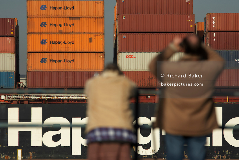 Shipping spotters train binoculars on a Hapag-Lloyd container cargo ship navigating downstream on the River Thames.