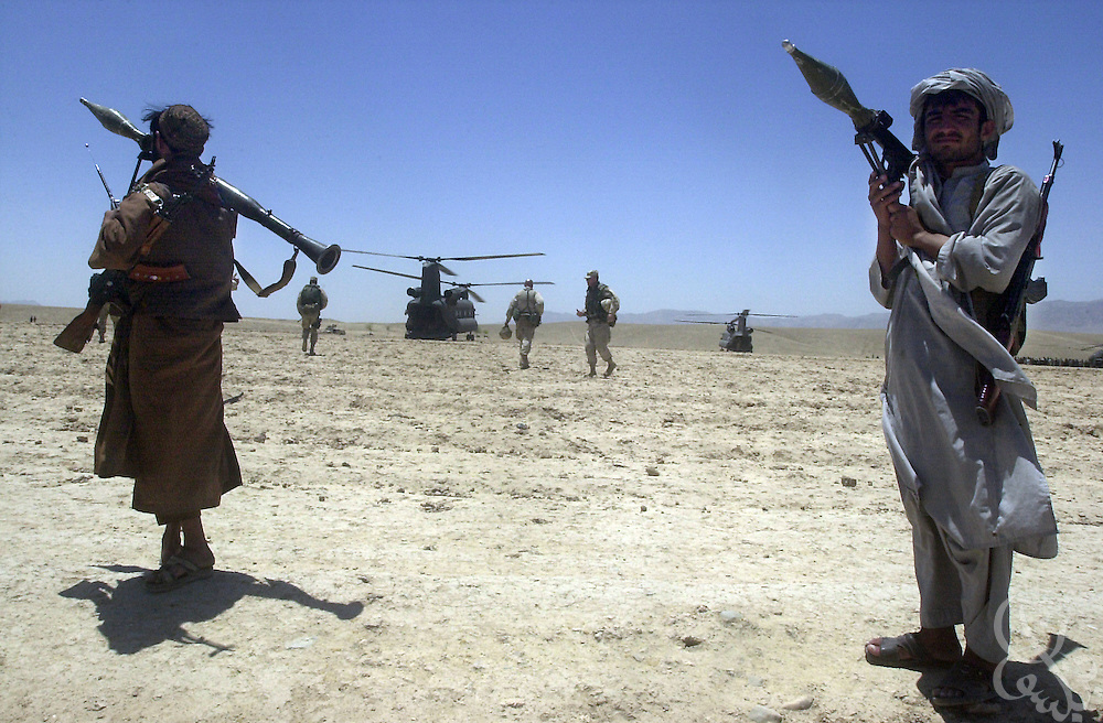 Local Afghan gunmen hold rocket propelled grenade launchers (RPG) as they guard a U.S. chinook helicopter during the July 7, 2002 visit by U.S. Army Gen. Dan Mcneill, commander of the Coalition Joint Task Force (CJTF 180), to Deh Rawud in Southern Afghanistan. McNeill used the visit to speak with local leaders about the possibility of stationing more U.S. troops in the region, following an incident last week in which U.S. aircraft mistakenly targeted Afghan civilians celebrating in the village.