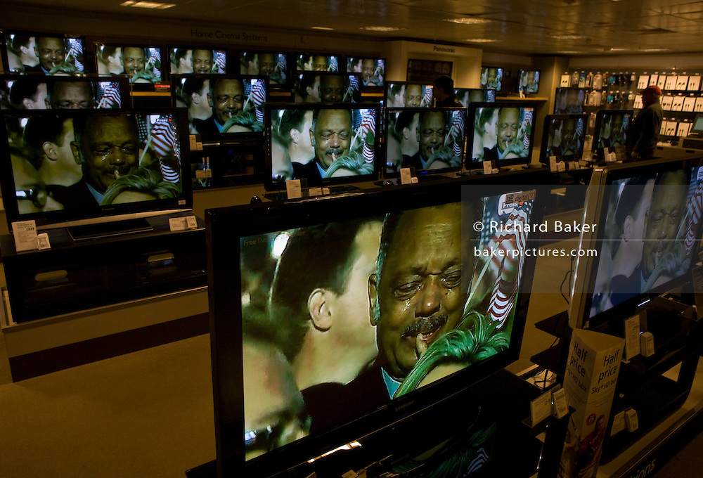 Live BBC news is being broadcast on TV screens in the John Lewis department store in Oxford Street, London, England. The Reverend Jesse Jackson who once stood next to Martin Luther-King during the days of segregation and racial discrimination sobs with tears falling down his face at Barack Obama's victory rally before party faithful at a rally in Chicago. His face is large on the many home cinema screens seen across the world's media after this historic political election which saw the election of America's first black Commander in chief. A shopper stops to watch the lunchtime news programme as Jackson weeps with joy thinking of the changes promised to bring to America while the rest of the world looks on hoping for new political directions.