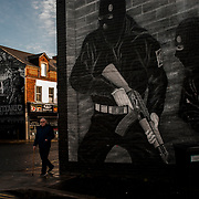 A local man passes by a loyalist mural in Newtownards Road, a predominately protestant and loyalist neighbourhood in East Belfast, Northern Ireland.