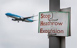 © Licensed to London News Pictures. 05/06/2018. London, UK. A passenger jet comes into land at Heathrow's northern runway in sight of a placard saying 'Stop Heathrow Expansion'. An announcement regarding expansion of the airport is expected today. Photo credit: Peter Macdiarmid/LNP