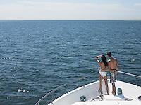 Young couple standing on bow of yacht looking at seascape back view