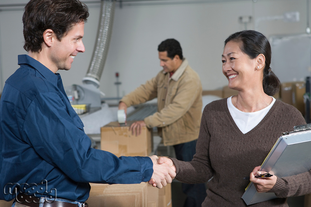 Man and woman shaking hands in distribution warehouse