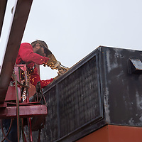Richard Fair, of Sign Art, breaks down the old sign in sections with a cutting torch, at the University of New Mexico-Gallup on Tuesday.