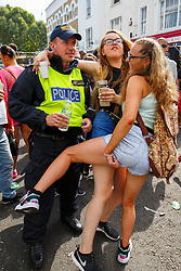 © Licensed to London News Pictures. 29/08/2016. London, UK. Revellers dance with a police officer on the second day of Notting Hill Carnival in west London, Monday 29 August 2016. Photo credit: Tolga Akmen/LNP