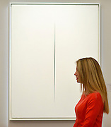 "© Licensed to London News Pictures. 31/01/2013. London, UK A woman stands in front of Lucio Fontana's .""Concetto Spaziale, Attesa. Expected to raise 2,200,000 -.2,800,000 GBP. Preview of highlights from Sotheby's forthcoming February sales of Impressionist & Modern Art and Contemporary Art in London, including works by Picasso, Bacon, Monet, Richter and Miró. Photo credit : Stephen Simpson/LNP"