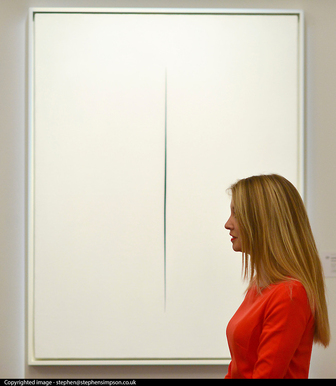 """© Licensed to London News Pictures. 31/01/2013. London, UK A woman stands in front of Lucio Fontana's .""""Concetto Spaziale, Attesa. Expected to raise 2,200,000 -.2,800,000 GBP. Preview of highlights from Sotheby's forthcoming February sales of Impressionist & Modern Art and Contemporary Art in London, including works by Picasso, Bacon, Monet, Richter and Miró. Photo credit : Stephen Simpson/LNP"""